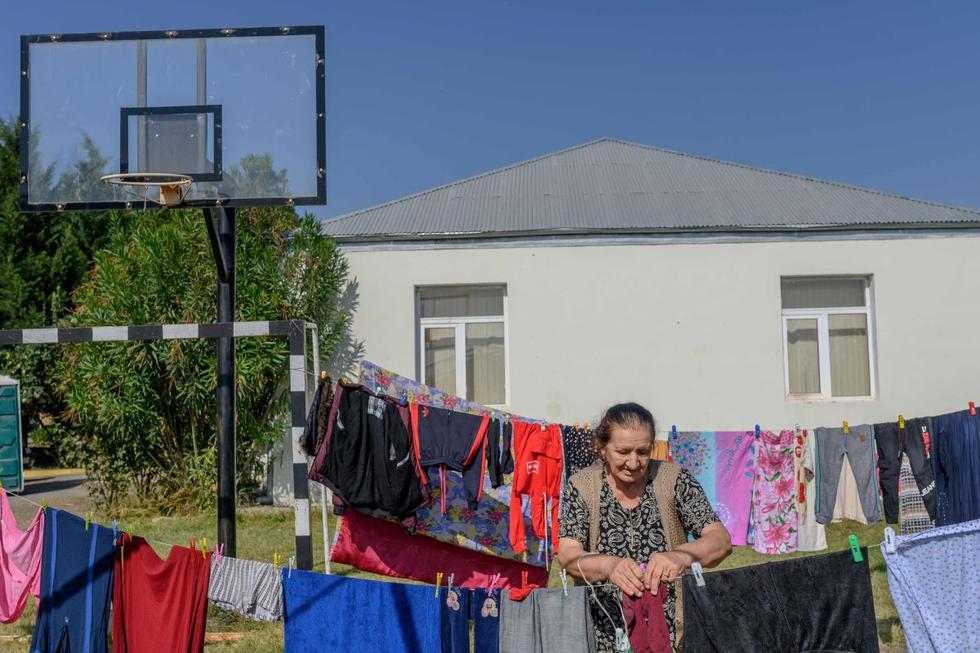 Fatma Suleymanova, una refugiada de 80 años que huyó de Terter debido al conflicto militar en curso entre Armenia y Azerbaiyán sobre la región separatista de Nagorno-Karabaj, cuelga ropa en una cuerda en el jardín de una escuela secundaria en la ciudad de Barda. (AFP/Bulent Kilic).