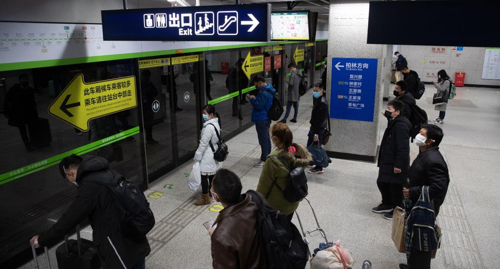 Los pasajeros con máscaras protectoras esperan para tomar un tren subterráneo en Wuhan. La ciudad reanudó parcialmente los servicios de transporte. (EFE).