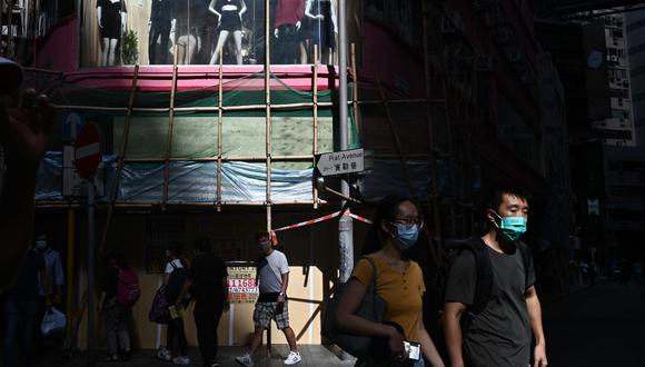 Un grupo de peatones caminan portando mascarillas en una concurrida vía en Hong Kong. (Anthony WALLACE / AFP)