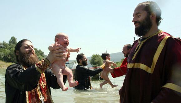 Sacerdotes ortodoxos georgianos bautizan a niños en el río Aragvi, en las afueras de Tbilisi, EL 13 de julio de 2007. Foto de SANDRO SHAMANIDZE / AFP).