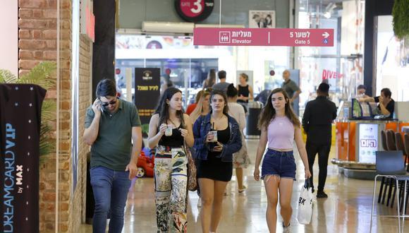 Los compradores sin mascarilla caminan en el centro comercial Dizengoff en la ciudad costera israelí de Tel Aviv, Israel, el 15 de junio de 2021. (Foto de JACK GUEZ / AFP).