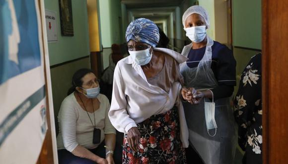 Un trabajador de la salud asiste a una anciana antes de recibir una inyección que contiene la vacuna Pfizer en el centro de atención frágil de Holy Cross Home en Pretoria. (Foto: Phill Magakoe / AFP).