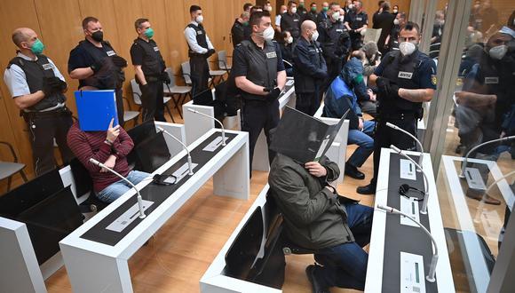 Los miembros del Grupo S se tapan los rostros durante el juicio que se les sigue. (Foto: EFE).