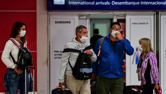 Pasajeros con mascarilla como medida preventiva contra la propagación del coronavirus (COVID-19) arriban al Aeropuerto Internacional de Ezeiza en Buenos Aires, el 12 de marzo de 2020. (RONALDO SCHEMIDT / AFP).