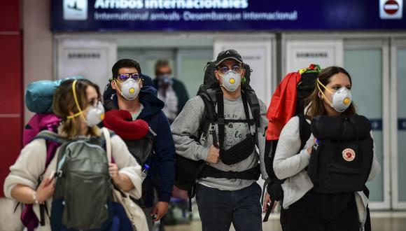 Pasajeros con mascarilla como medida preventiva contra el coronavirus COVID-19 arriban al Aeropuerto Internacional de Ezeiza en Buenos Aires, Argentina, el 12 de marzo de 2020. (Foto referencial, Ronaldo SCHEMIDT / AFP).