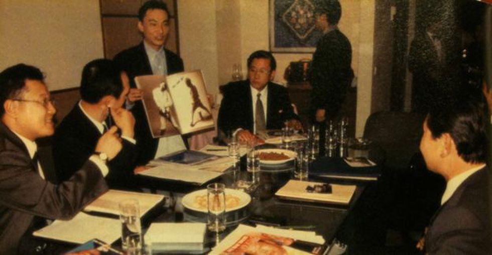 Park, haciéndose pasar por un ejecutivo de una firma publicitaria, le explica a los norcorearos una campaña de publicidad.