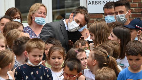 El presidente de Francia, Emmanuel Macron, posa con alumnos de la escuela primaria en Poix-de-Picardie. (EFE / EPA / DENIS CHARLET).