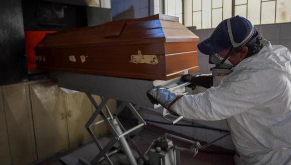Un empleado traslada el ataúd de una persona fallecida por el coronavirus COVID-19 a un incinerador en el cementerio de Zipaquirá, en Colombia, el 15 de junio de 2021. (Foto de Raúl ARBOLEDA / AFP).