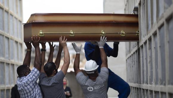 Operarios y familiares introducen el féretro con los restos de una mujer que murió por complicaciones del COVID-19 en un nicho en el cementerio de Inahuma, en Río de Janeiro, Brasil, el 13 de abril de 2021. (AP Foto/Silvia Izquierdo).