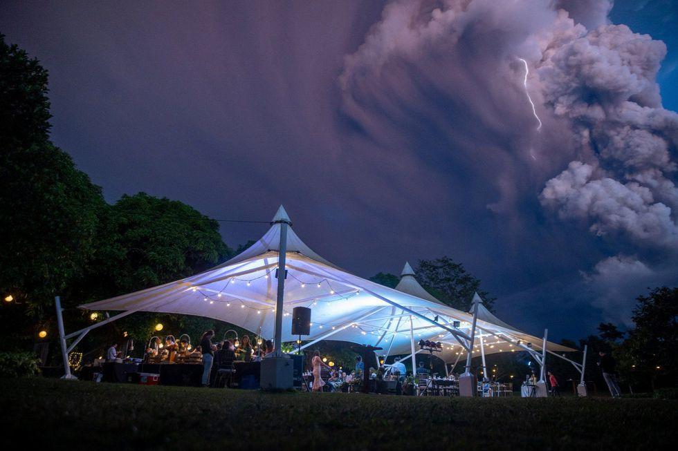 La gente asiste la boda mientras el volcán Taal envía una columna de cenizas en Alfonso, Cavite, Filipinas. (Reuters).