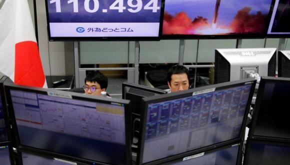 Los empleados de la bolsa de valores trabajan frente a sus pantallas, de fondo pararece el tipo de cambio del yen japonés a dólar estadounidense en Tokio. (Foto: Reuters/Toru Hanai)