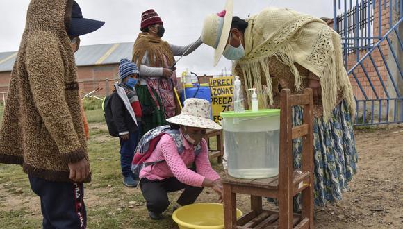 Mujeres indígenas aymaras desinfectan y lavan las manos de los estudiantes antes de ingresar a la escuela durante su primera semana de clases presenciales en el colegio Ladislao Cabrera, en la comunidad de Machacamarca. (Foto de AIZAR RALDES / AFP).