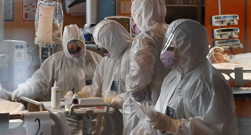 Trabajadores médicos en un tendón de equipo de protección (trasero R) el 24 de marzo de 2020 en la nueva unidad de cuidados intensivos de 3 niveles para casos COVID-19 en el hospital Casal Palocco cerca de Roma. (AFP)