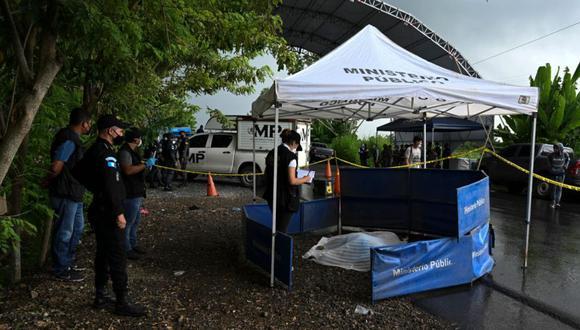 Fiscales del Ministerio Público recolectan evidencia cerca del cuerpo de un migrante no identificado que murió al caer accidentalmente de un camión luego de cruzar en una caravana desde Honduras en su camino a los Estados Unidos, en Entre Ríos, Guatemala. (Foto: AFP / Johan ORDONEZ).