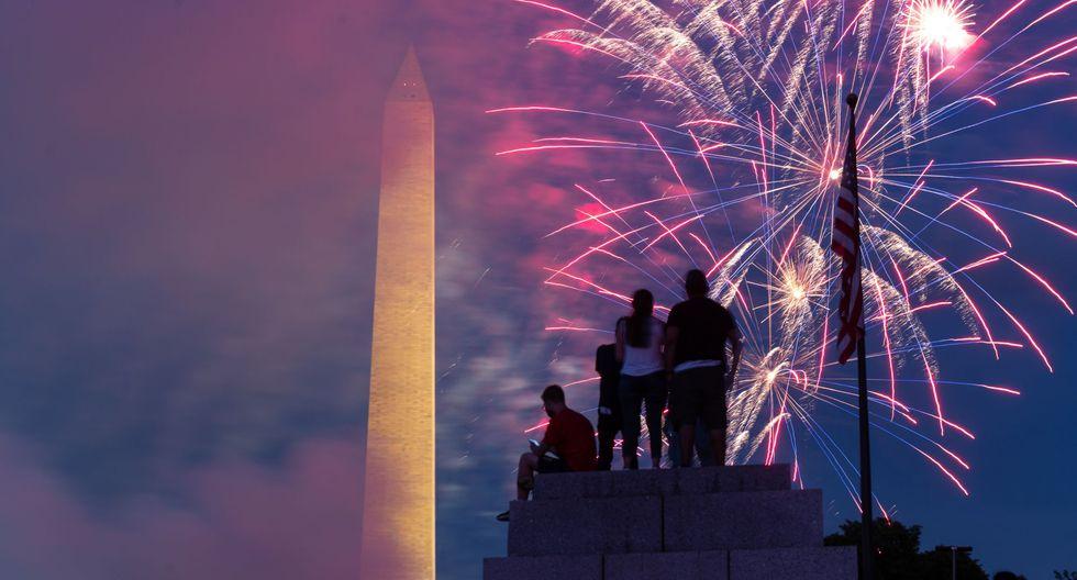 El público se sienta en la cima de un pilar en el Memorial de la Segunda Guerra Mundial mientras los fuegos artificiales estallan en Washington, DC durante las celebraciones por el Día de la Independencia de Estados Unidos. (Foto de ROBERTO SCHMIDT / AFP).
