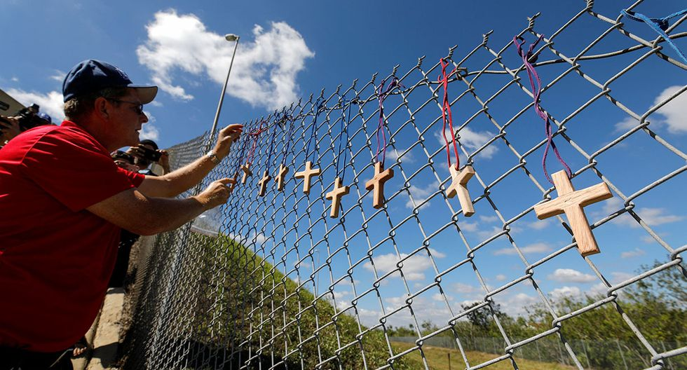 Bob Ossler, chaplain with the Cape Coral volunteer fire department, places seventeen crosses for the victims of yesterday's shooting at Marjory Stoneman Douglas High School on a fence a short distance from the school in Parkland, Florida, U.S., February 15, 2018. REUTERS/Jonathan Drake
