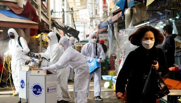 Una mujer con mascarilla camina mientras se produce una fumigación en plena crisis por el coronavirus en Corea del Sur. Foto: Reuters