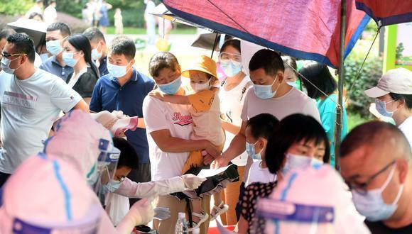 Personas se acercan a un lugar de descarte de coronavirus, en Wuhan. EFE
