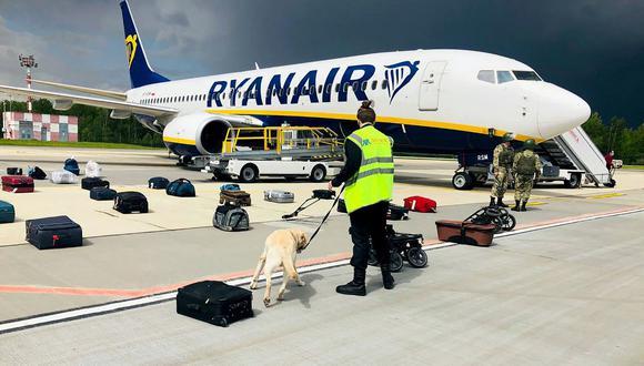 Un adiestrador de perros bielorruso revisa el equipaje de un avión de Ryanair que fue obligado a aterrizar de emergencia. (Foto: AFP).