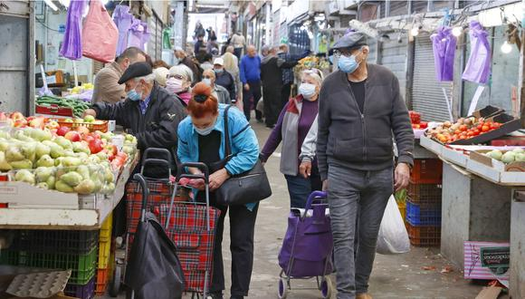Israelíes, con mascarillas debido a la pandemia de COVID-19, compran en el mercado central de la ciudad costera de Netanya en Israel, el 27 de diciembre de 2020. (Foto: Jack Guez/ AFP).