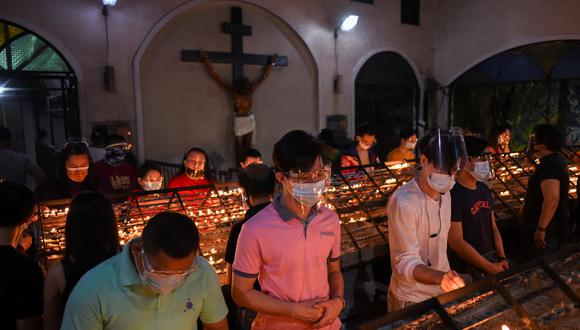 En Manila, Filipinas, un grupo de feligreses usan mascarilla mientras rezan. REUTERS/Lisa Marie David