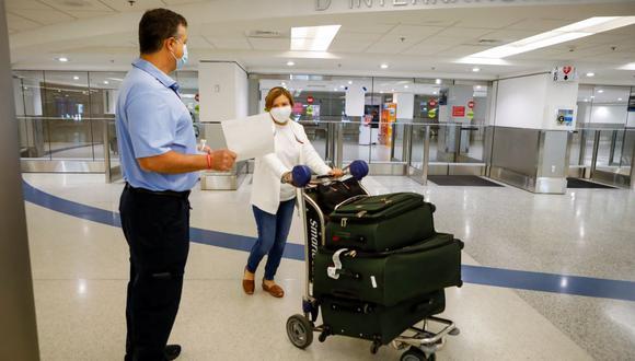Un trabajador informa sobre vacunas gratuitas Johnson & Johnson contra el coronavirus covid-19 en el área de llegadas internacionales del Aeropuerto Internacional de Miami, Estados Unidos, el 29 de mayo de 2021. (EVA MARIE UZCATEGUI / AFP).