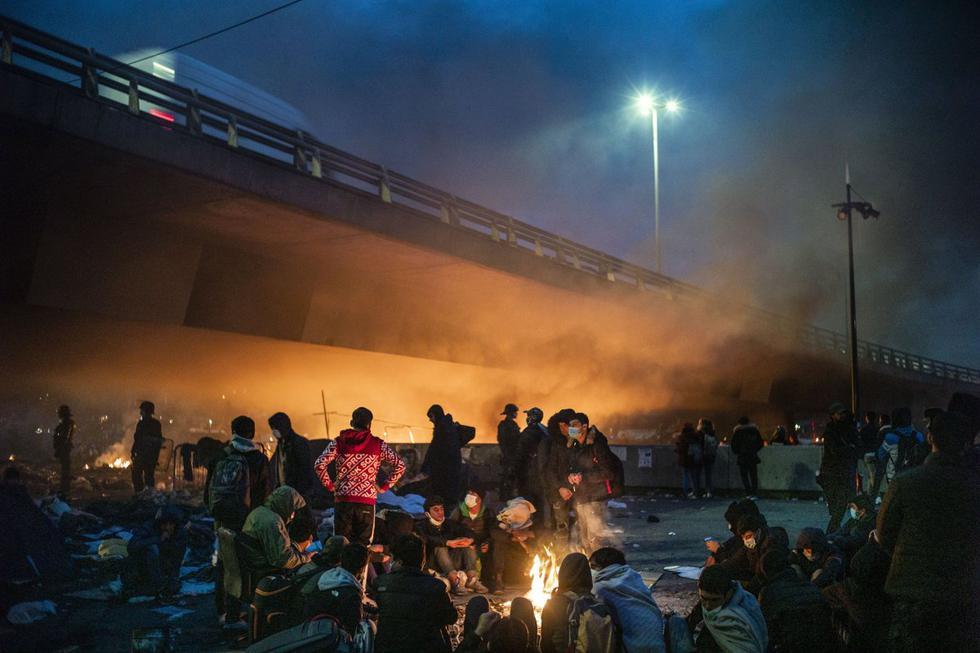 Los migrantes prendieron fuego a diversos objetos para calentarse mientras esperaban ser evacuados por las fuerzas policiales en Saint-Denis, al norte de París, Francia. (EFE/EPA/YOAN VALAT).