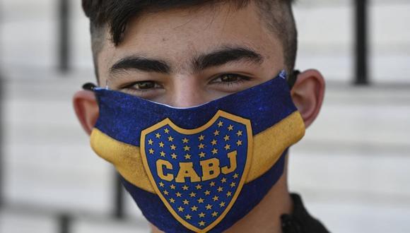Un joven posa con una mascarilla del equipo argentino de fútbol Boca Juniors en Villa Fiorito, en las afueras de Buenos Aires, Argentina, el 3 de agosto de 2020, en medio de la pandemia de coronavirus. (JUAN MABROMATA / AFP).