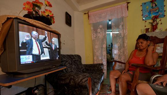 Una mujer mira televisión en su casa de La Habana cuando el saliente presidente cubano, Raúl Castro, levanta el brazo del nuevo presidente, Miguel Díaz-Canel, luego de que la Asamblea Nacional lo nombra formalmente.