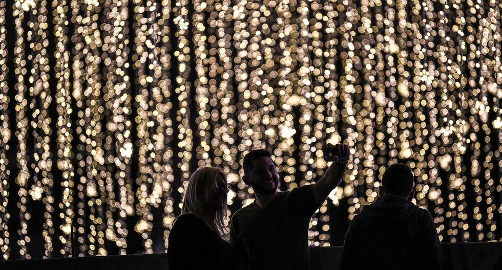 Una pareja posa para un selfie frente a las luces de Navidad colocadas en el río Guaire en Caracas. (AFP / Yuri CORTEZ).