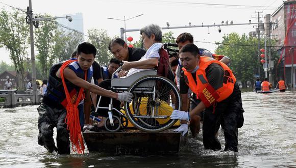 Miembros del equipo de rescate trasladan a una anciana en silla de ruedas por una carretera inundada tras las fuertes lluvias en Xinxiang, en la provincia de Henan, en el centro de China, el 23 de julio de 2021 (Foto: JADE GAO / AFP).