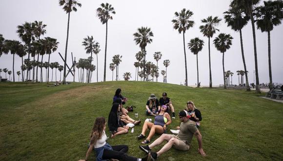 En esta foto del 5 de mayo del 2021, un grupo de amigos, que dicen estar plenamente vacunados contra el coronavirus pasan el rato en la playa en la sección de Venice en Los Ángeles, Estados Unidos. (AP Foto/Jae C. Hong.).