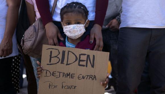 Dareli Matamoros, una niña de Honduras, sostiene un cartel pidiendo al presidente Biden que la deje entrar a Estados Unidos durante una manifestación en San Ysidro, Tijuana. (Foto de Guillermo Arias / AFP).