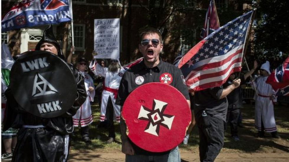 Supremacistas blancos portan símbolos del Ku Kux Klan. Al fondo, un cartel dice que los judíos son hijos de Satanás.