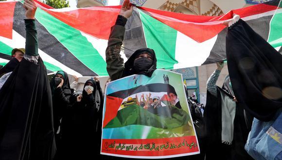 Manifestantes iraníes ondean banderas nacionales palestinas durante una protesta en Teherán para condenar la campaña aérea israelí en curso en Gaza. (Foto de ATTA KENARE / AFP).