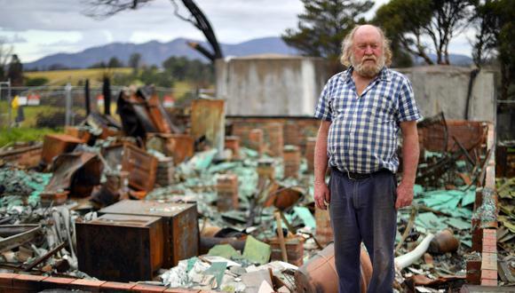 Esta imagen, tomada el pasado de mayo de 2020, muestra a Wayne Keft, de 66 años, parado frente a las ruinas de su casa destruidas durante los incendios forestales cerca de Cobargo, una ciudad en la costa sur del estado de Nueva Gales del Sur. Las víctimas de los catastróficos incendios forestales de Australia todavía viven en tiendas de campaña, garajes y refugios improvisados expuestos a la pandemia del COVID-19. (Saeed KHAN / AFP).