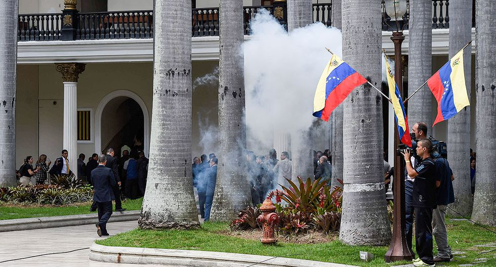 Supporters of Venezuelan President Nicolas Maduro storm the National Assembly building in Caracas on July 5, 2017 as opposition deputies hold a special session on Independence Day. A political and economic crisis in the oil-producing country has spawned often violent demonstrations by protesters demanding President Nicolas Maduro's resignation and new elections. The unrest has left 91 people dead since April 1. / AFP / Juan BARRETO