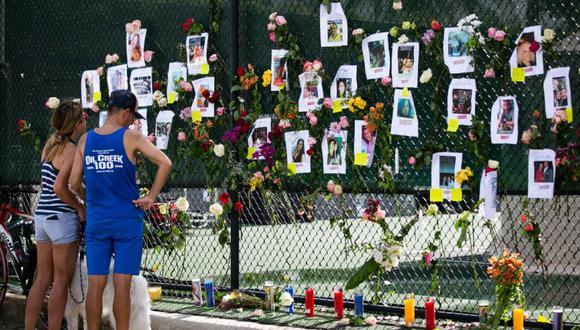 Cheri Fine (izquierda) y Mark (sin apellido) visitan un memorial improvisado en el sitio de un edificio derrumbado en Surfside, Florida, al norte de Miami Beach. (Foto: Andrea SARCOS / AFP).