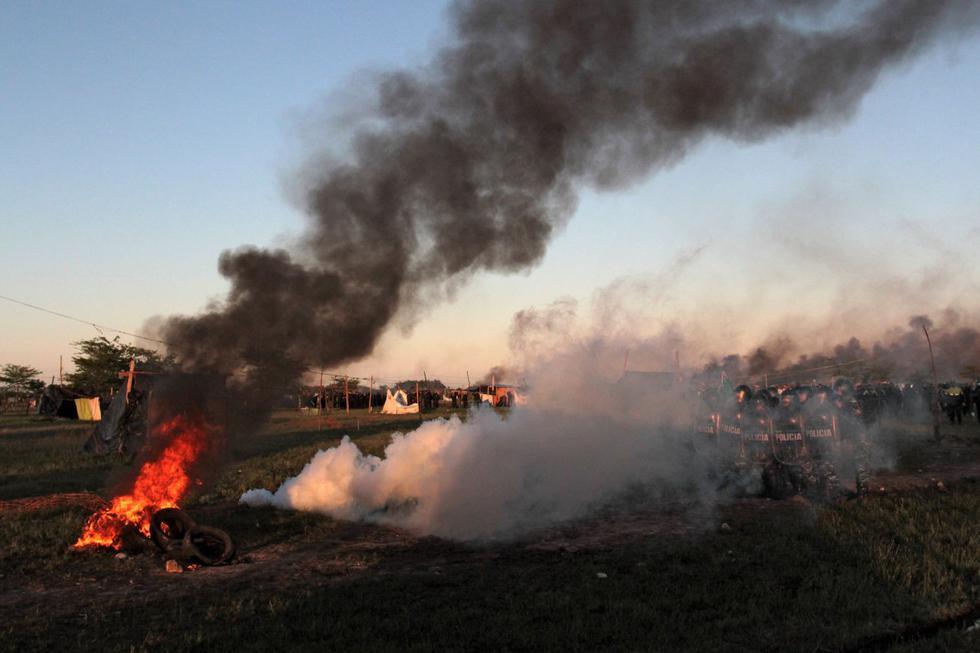 La policía antidisturbios toma posición cerca de un incendio provocado por ciudadanos durante un desalojo de tierras en Guernica, provincia de Buenos Aires, Argentina, el 29 de octubre de 2020.  (AFP).