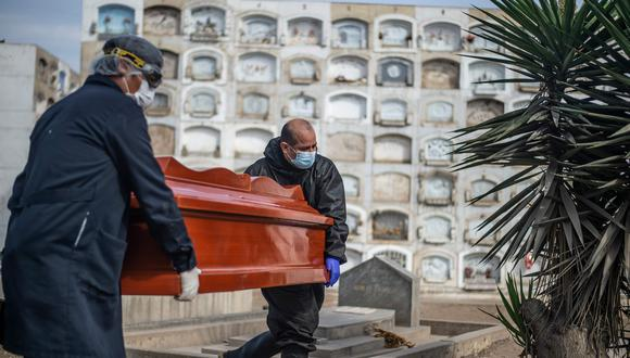 Los trabajadores llevan un ataúd con el cuerpo de una víctima de COVID-19 en el cementerio El Angel, en Lima. (AFP / ERNESTO BENAVIDES).