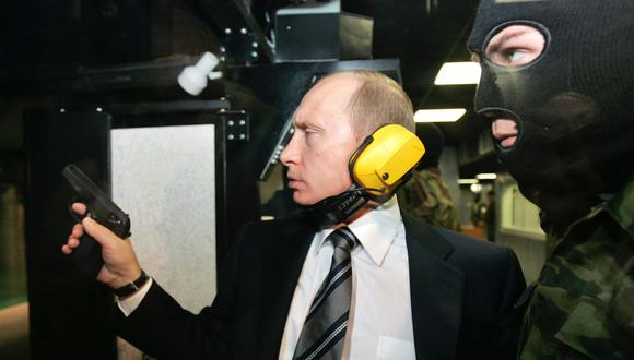 El presidente ruso Vladimir Putin y un guardia enmascarado practican tiro en un edificio del GRU. (Reuters).