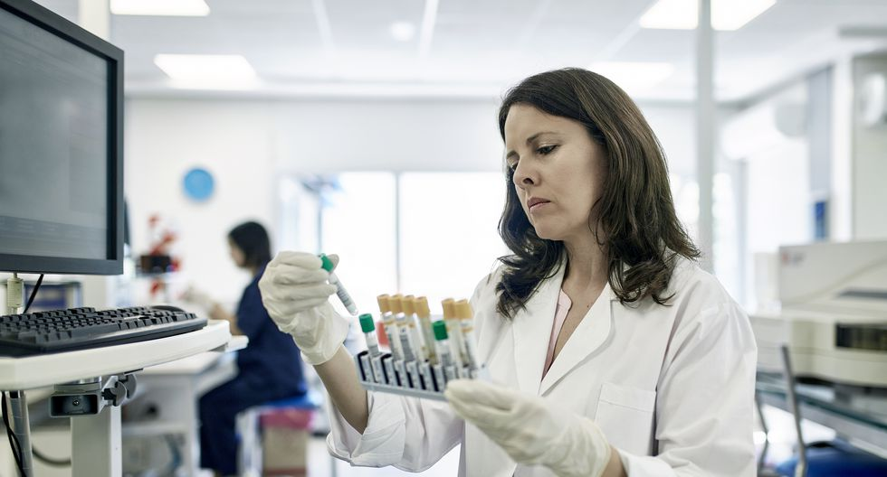 Close-up of serious Hispanic female pathologist in white coat examining test tube rack samples in Buenos Aires clinical analysis laboratory.