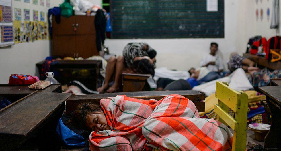 A woman displaced by flash floods sleeps on school chairs inside an evacuation center in Marikina, Metro Manila, in Philippines, August 13, 2018. REUTERS/Eloisa Lopez
