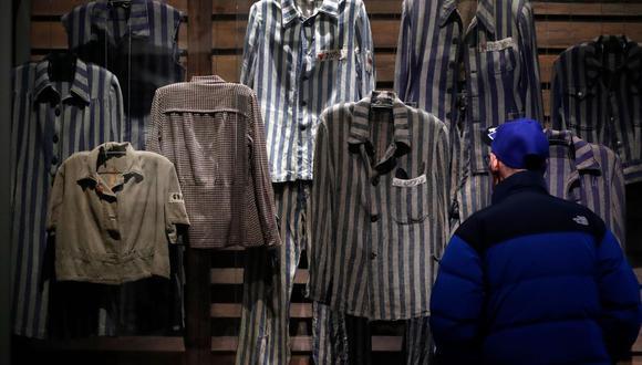 Un hombre mira fijamente los uniformes que utilizaron los prisioneros nazis, mayormente judíos, recluidos en los campos de concentración durante la Segunda Guerra Mundial, ahora expuestos en el Museo del Holocausto Yad Vashem, en Jerusalén. (Foto: AFP)