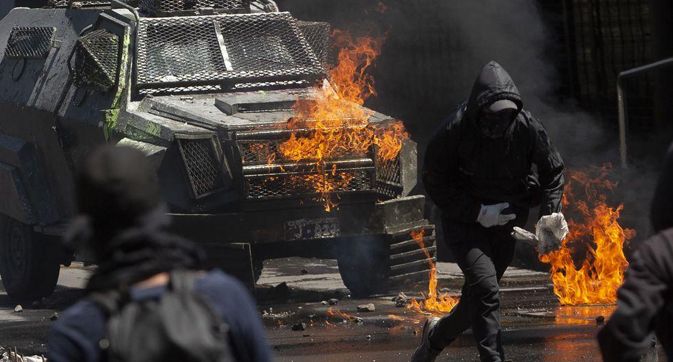Manifestantes arrojan bombas molotov contra manifestantes. (Photo by CLAUDIO REYES / AFP).