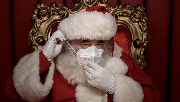 Una persona vestida de Papá Noel con mascarilla para evitar contagios de coronavirus, espera la visita de niños esta mañana en un centro comercial. (Foto referencial: EFE/Biel Aliño).