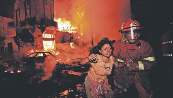 Aquella trágica noche una mujer fue rescatada por los bomberos en el cruce de los jirones Andahuaylas y Cusco, según esta fotografía del archivo histórico de El Comercio. Hubo más de 500 heridos. (Foto: Daniel Silva/Archivo El Comercio)
