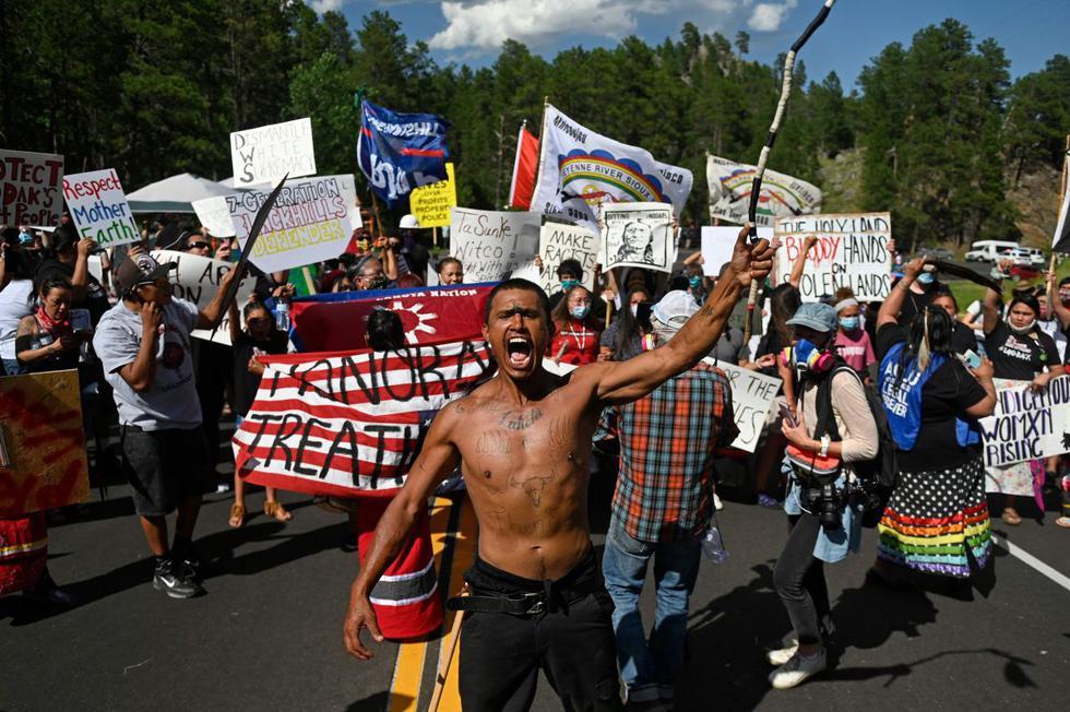 Activistas y miembros de diferentes tribus de la región bloquean un camino mientras protestan en Keystone, Dakota del Sur, el 3 de julio de 2020, durante una manifestación alrededor del Monumento Nacional Mount Rushmore y la visita del presidente de los Estados Unidos, Donald Trump. (AFP/ ANDREW CABALLERO-REYNOLDS)