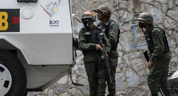 Members of the Bolivarian National Guard (GNP) hide behind an armored vehicle during clashes with members of a criminal gang near La Cota 905 in Caracas.  (Yuri Cortes / AFP).