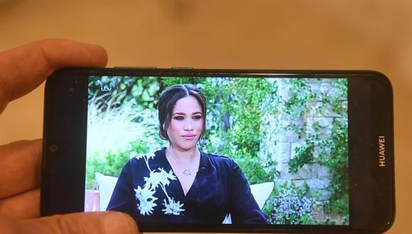 Una persona mira en un teléfono móvil la retransmisión en Reino Unido de la entrevista a Meghan Markle y el príncipe Harry. (EFE / EPA / FACUNDO ARRIZABALAGA).